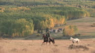 MS TS ZO Horse & Riders Riding in front of Yellow Aspen Grove with Colorado Rocky Mountains and Wilson Peak / Telluride, Colorado, United State