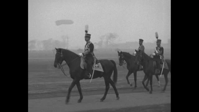 Horseman leads others on road / hundreds of soldiers / Hirohito aka Emperor Showa on horse leading group / crowd of men some in decorate headgear...