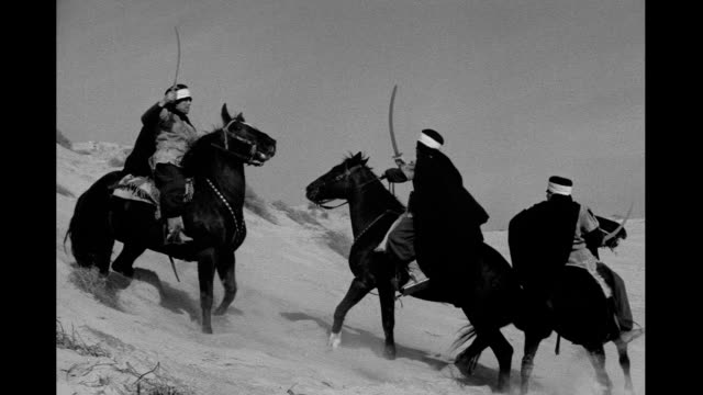 Horsemen in desert waving swords riding down dune and into distance Desert warriors on January 01 1930