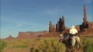 Horsemen ride away from camera towards tall thin buttes Available in HD.