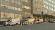 MS Hospital building with parked ambulances and passing traffic / New York, New York, USA