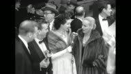 ABC host Dennis James hostess Maggi McNellis in a mink stole speaks with Faye Emerson wearing a full fur coat Emerson's husband Skitch Henderson to...
