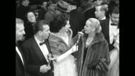 ABC host Dennis James hostess Maggi McNellis in a mink stole with Faye Emerson wearing a full length fur coat speaking about people attending...