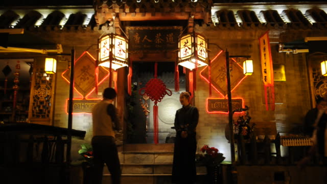 A hostess encourages a possible customer at Lake Houhai's Old Tea House.