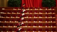 Hostesses fill up cups of tea prior to the opening of the Chinese People's Political Consultative Conference at the Great Hall of the People in...