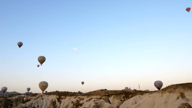 Heißluftballons fliegen über die Feenkamine mit Hintergrund Uchisar Castle in Cappadocia