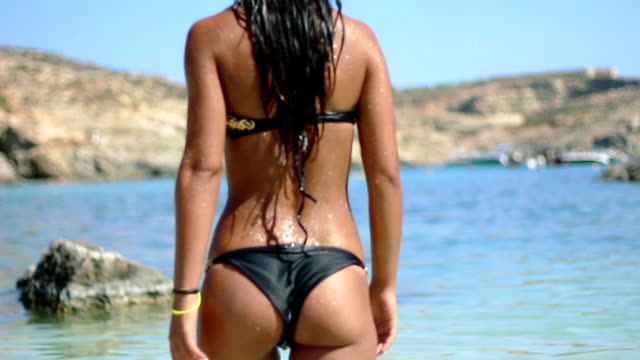 Hot girl enters a transparent sea water on a blue lagoon