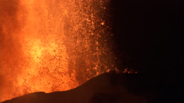 Hot lava spews into the air from a volcanic eruption. Available in HD.