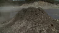 Hot mud bubbles inside a small mound near a geothermal pool Available in HD.