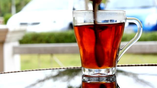Hot tea, spoon stirring sugar in tea