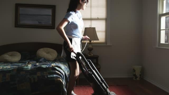 hotel maid singing and dancing while vacuuming