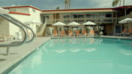 LA TS hotel pool at mid-century modern boutique resort with lounge chairs and umbrellas