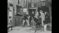 A hotel receptionist leads a group of people into a room and bellhop Buster Keaton throws their luggage behind the desk before returning to mopping