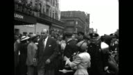 EXT Hotel Theresa in Harlem Manhattan with crowds gathered in front cars passing in foreground / MS singer Josephine Baker with police escort makes...
