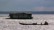 WS House on Amazon River, man with two children in traditional rowboat in foreground / Tefe, Amazonas, Brazil