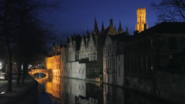 WS Houses and tower reflecting in canal at night / Bruges, West Flanders, Belgium
