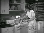 B/W 1948 housewife at stove cooking / industrial