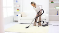 Housewife cleaning the room with vacuum cleaner.