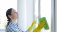 Housewife cleaning window with green mop