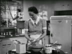 B/W 1938 housewife cooking in kitchen breaking eggs into bowl / educational / industrial
