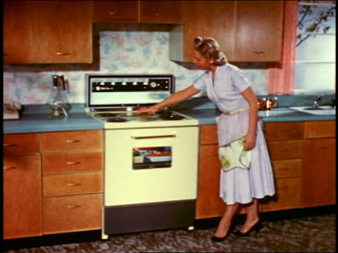 1958 housewife demonstrating features of stove/oven with wave of hand / opening oven