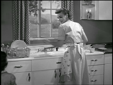 B/W 1952 REAR VIEW housewife doing dishes / girl comes up + gives her glass of water / industrial