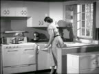 B/W 1950 PAN housewife entering kitchen / puts on apron + stirs pot on stove / opens refrigerator