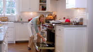 Housewife enters kitchen, takes turkey out of oven and smells, closes oven door (dolly-shot)