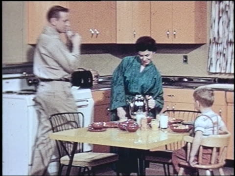 1957 housewife in bathrobe serving breakfast / father enters + sits at table with son