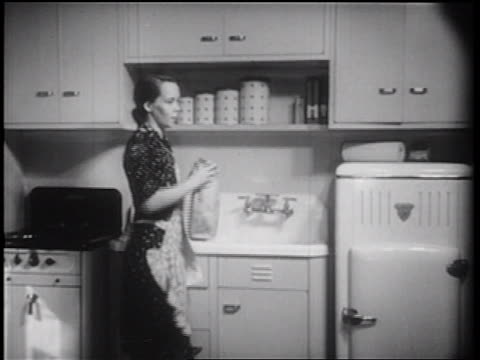 B/W 1939 housewife in kitchen handing son lunch bag as he opens refrigerator / documentary