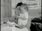 Housewife w/ baby girl in arms stuffing paper into envelopes CU Woman writing name address on envelope Clerical pamphlets Virginia Americana Suburbia