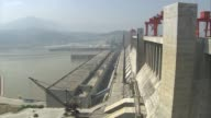 Three Gorges Dam Engineers in hardhats working on top of dam with large industrial cranes all around general view of reservoir side of dam with large...