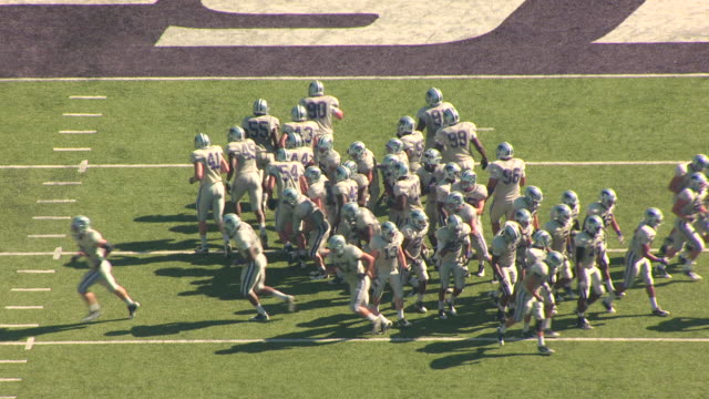 MS AERIAL Huddle of football players in uniform at Billy Snyder Family Stadium / Manhattan, Kansas, United States