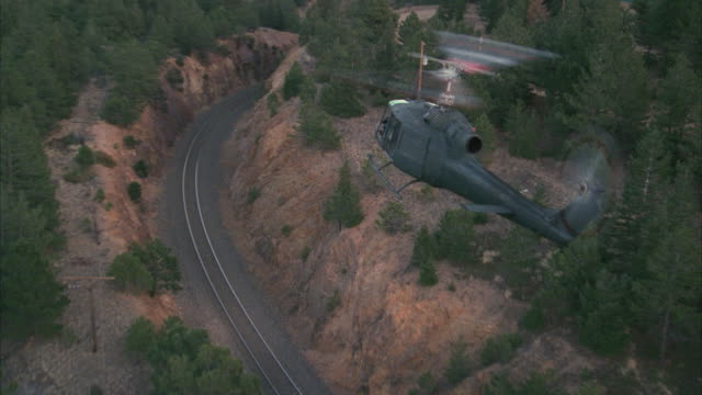AERIAL Huey helicopter flying over rail track and shining searchlight