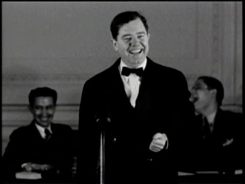 Huey Long laughing on stage during a speech / Two men sitting behind Huey Long laughing along with him /