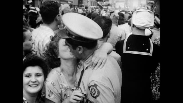 / Huge American flag waved above the packed crowd in Times Square / suited man crowd surfing / woman kisses soldier intensely / soldiers drinking...
