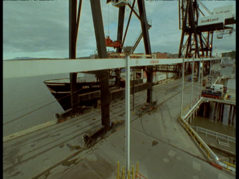 Huge cranes roll into position and remove containers from ship onto waiting lorries, Anchorage, Alaska