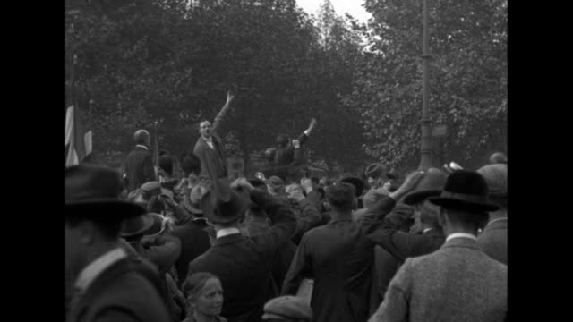 MS huge crowd of men in park or plaza / Josef Friedrich Matthes and 3 other men stand on platform and lead crowd in cheer / CU Matthes / MS Matthes...