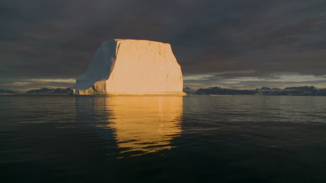 Huge iceberg floating at midnight sun in Greenland