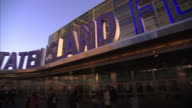 Huge letters spell out Staten Island Ferry where pedestrians pass by.