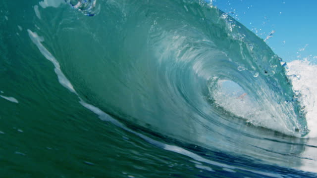Huge perfect barreling beautiful wave POV as wave breaks over camera on shallow sand beach in the California summer sun. Shot in slowmo on the Red Dragon at 300FPS.