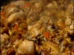 Huge pot of paella containing fish chicken and vegetables bubbles in its own delicious juices Spain