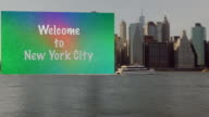 Huge Welcome to New York City sign dragging after boat