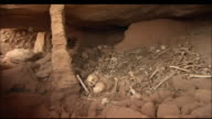 Human bones lie piled in a cave. Available in HD.