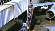 WS, HA, Human chain of ground crew handing parcels up staircase towards aircraft, Los Angeles, California, USA