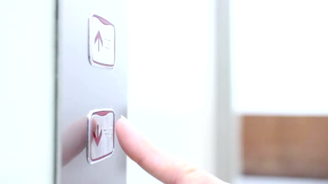 Human finger presses the button for an elevator