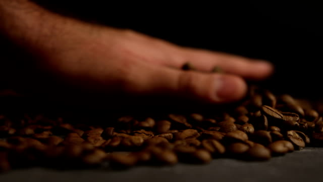 Human hand and coffee beans