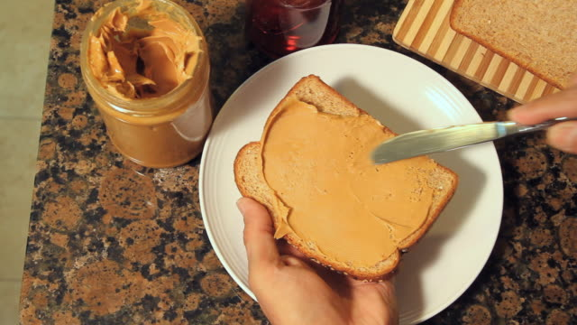 CU Human hand applying peanut butter and jelly on bread / Miami, Florida, USA