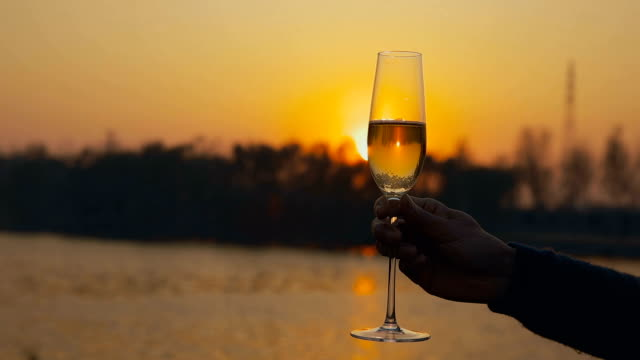Human hand holding glass of champagne at sunset