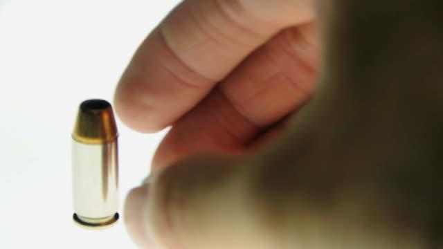 CU Human hand placing bullet on light table / Los Angeles, California, USA